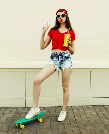 Young woman with green skateboard wearing a shorts and red baseball cap in a city