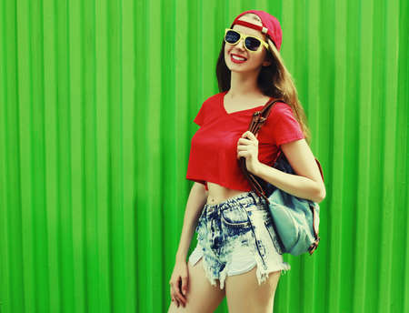Portrait of happy smiling young woman wearing a shorts, red baseball cap and backpack in a city
