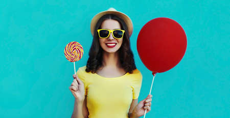 Portrait of happy smiling woman with lollipop and red balloon wearing a summer straw hat on a blue background