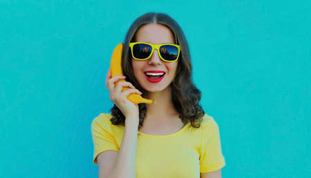 Portrait of funny woman calling on a banana phone on a blue background Stok Fotoğraf