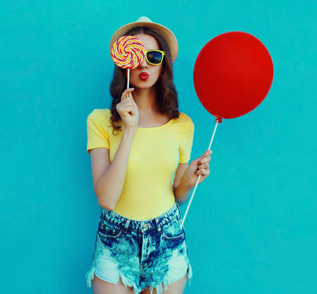 Portrait of woman with lollipop and red balloon blowing a red lips wearing a summer straw hat on a blue background Stok Fotoğraf
