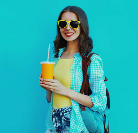 Portrait of happy smiling young woman with cup of juice on a blue background Stok Fotoğraf