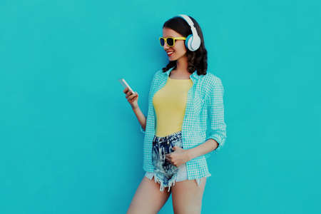 Portrait of happy smiling young woman with phone and wireless headphones listening to music on a blue background Stok Fotoğraf