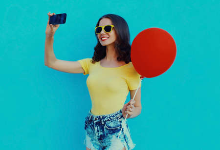 Portrait of woman with red balloon taking selfie by smartphone on a blue background