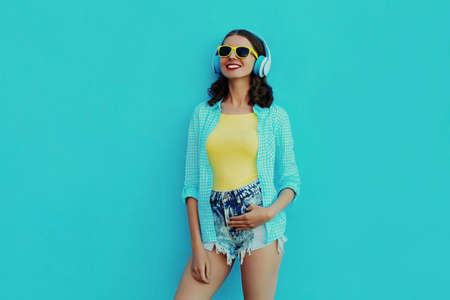 Portrait of happy young woman with wireless headphones listening to music on a blue background