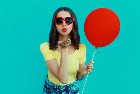 Portrait of woman with lollipop and red balloon blowing a red lips on a blue background