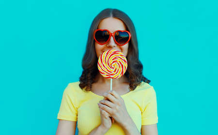 Portrait of young woman covering her lips with lollipop on a blue background