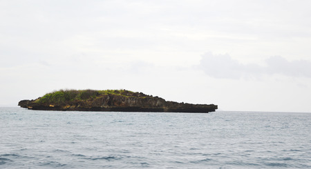 uninhabited: Rocky uninhabited island plateau cliff in ocean with clouds, sky & horizon in background