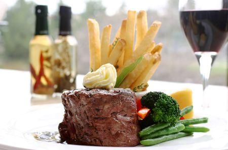 gourmet dinner: 8 oz Tenderloin Steak cubierto con mantequilla de trufas. Servido con br�coli, frijol, r�bano picante y fritas. Tel�n de fondo de un vaso de vino tinto. Someras DOF.