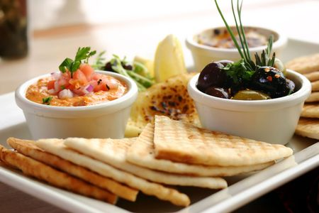 dipping: Sumptious platter of flat breads served with red pepper hummus dip, crab dip, olives and grilled haloumi cheese. Shallow DOF. Stock Photo