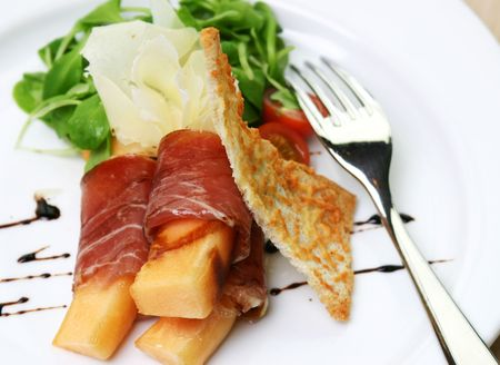 Procuitto ham rolled around fresh melon.  Drizzled with balsamic vinagrette and focaccia bread. Shallow DOF. Stock Photo - 220358