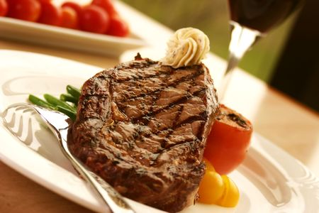 steak dinner: 12oz ribeye steak topped with truffle butter and grilled tomato. Served with red wine. Shallow DOF