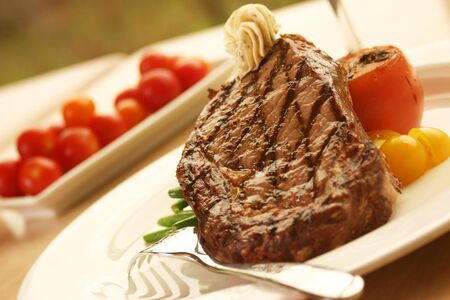 12oz ribeye steak topped with truffle butter and grilled tomato. Shallow DOF. Stock Photo - 220567