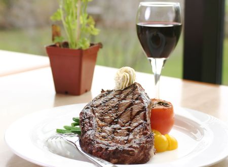 white wine: 12oz ribeye steak topped with truffle butter and grilled tomato. Served with red wine. Stock Photo