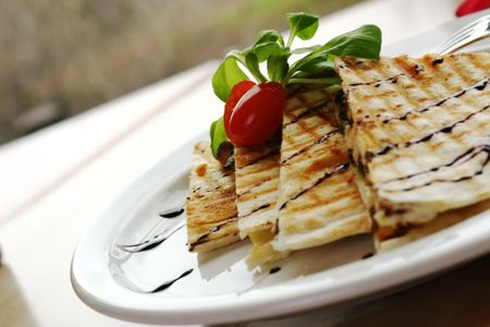 Three cheese chicken quesadilla, drizzeled with balsamic vinager. Shallow DOF photo