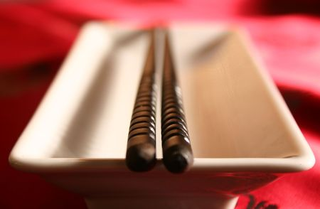 Chopsticks on a plate placed across a bowl in a formal dinner setting.