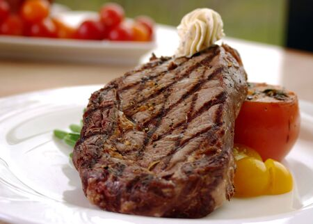 12oz ribeye steak topped with truffle butter and grilled tomato. Shallow DOF Stock Photo