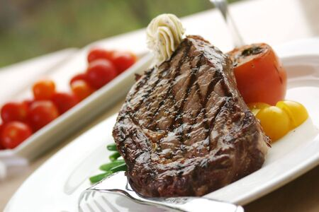 12oz ribeye steak topped with truffle butter and grilled tomato. Stock Photo