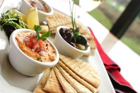 Sumptious platter of flat breads served with red pepper hummus dip, crab dip, olives and grilled haloumi cheese. Shallow DOF. Stock Photo