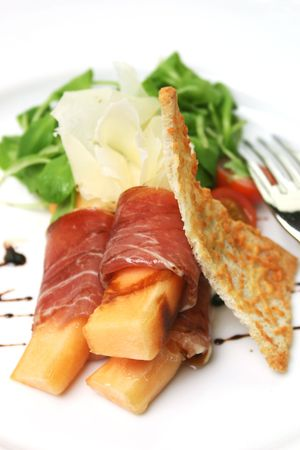balsamic: Procuitto ham rolled around fresh melon.  Drizzled with balsamic vinagrette and focaccia bread. Shallow DOF.