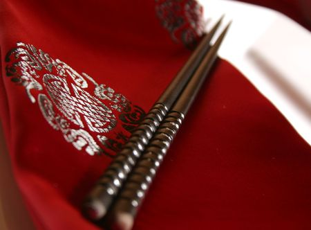 Chopsticks on a plate placed on a delicately embroidered table napkin. Formal dinner setting. Stock Photo