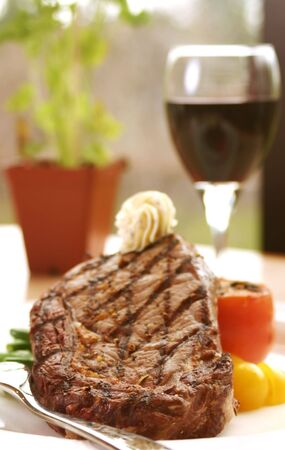 12oz ribeye steak topped with truffle butter and grilled tomato. Served with red wine. Shallow DOF. Stock Photo