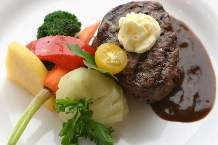 8 oz tenderloin steak dinner with an accompaniment of mashed potatoes, tomatoes, broccoli and butter. Shallow DOF. Reklamní fotografie