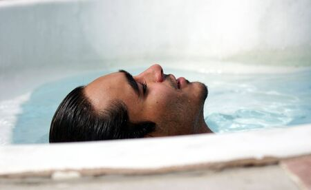 takes: An attractive man takes it easy in the pool Stock Photo