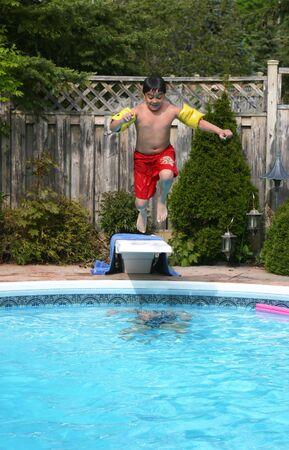 Jonge jongens springt in het zwembad van een duikplank.