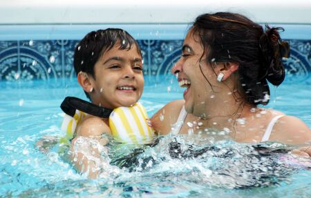 Mother and son having a great time in the pool. Shallow DOF. Stock Photo