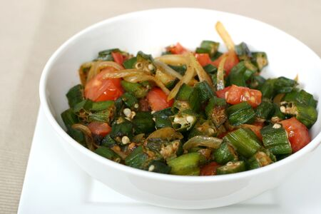 okra: Traditional Indian dish of Okra shallow fried with tomatoes, onions and spices. Shallow DOF. Stock Photo