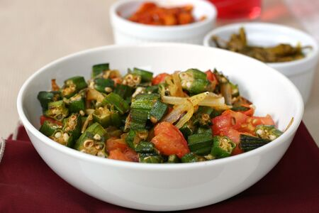 Traditional Indian dish of Okra shallow fried with tomatoes, onions and spices. Shallow DOF. Stock fotó