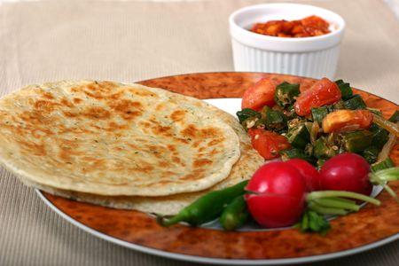 encurtidos: Comida india tradicional de los panes planos (rotis), del okra (bhindi) y de los r�banos. Los chiles y las salmueras son esencial en el lado. Foto de archivo
