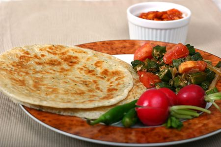 Traditional Indian meal of flat breads (rotis), okra (bhindi) and radishes. Chillies and pickles are essentials on the side. Stock Photo