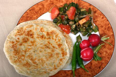 sottoli: Indiana tradizionale pasto di pane piatto (rotis), okra (bhindi) e ravanelli. Peperoncini e sottaceti sono essenziali sul lato.