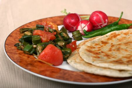 Traditional Indian meal of flat breads (rotis), okra (bhindi) and radishes. Chillies and pickles are essentials on the side.