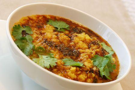 lenteja: Tradicional plato de lentejas indias. Fritos lentejas, cumin y adornado con hojas de menta. Someras DOF.