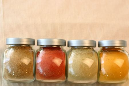 Indian spice jars containing garam masala, ground red chillies, ground cumin and turmeric.