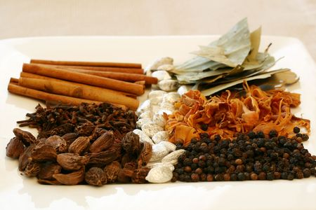 mace: An assortment of fragrant, richly flavored spices - bay leaves, mace, peppercorns, black pepper, silver cardamom pods, cloves and cinnamon. Focus on the front of the tray.