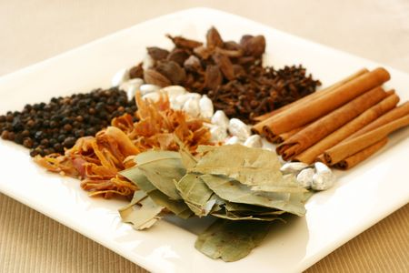 fragrant: An assortment of fragrant, richly flavored spices - bay leaves, mace, peppercorns, black pepper, silver cardamom pods, cloves and cinnamon. Focus on the bay leaves.