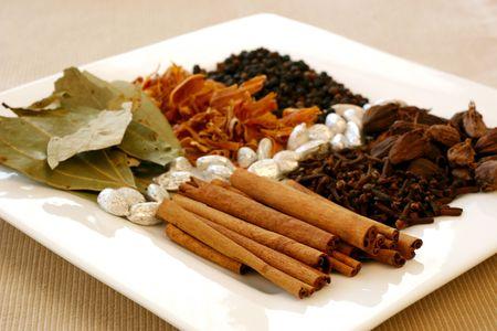 香り、風味豊かなスパイス - 月桂樹の葉、メイス、胡椒、黒胡椒、銀カルダモン ・ ポッド、クローブ、シナモンの品揃え。シナモンの棒に焦点を当 写真素材