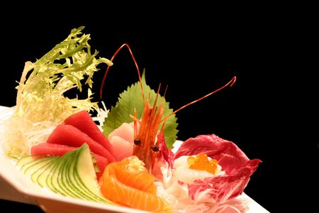 Assortment of sushi on a plate against a black background.