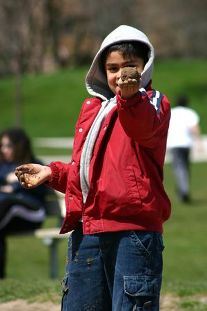 A young boy holds up a mudball in the park. photo