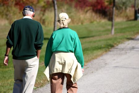 豪華な秋の朝の公園で散歩老夫婦。 写真素材