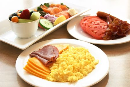 Exotic platter of scrambled eggs, deli beef, ham, sliced turkey & chicken and assorted cheese slices. Sausages, bacon and tomatoes on the side plate and a fruit bowl and salmon salad to complete the meal. photo