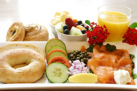 A healthy start breakfast comprising of salmon salad, bagels, fruit bowl and fresh orange juice.