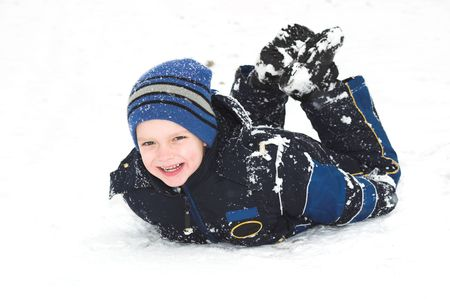A child smiles as he has the time of his life rolling in the snow.