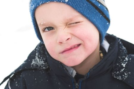 mischievious: A child winks while playing in the snow.