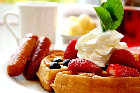 Blueberry waffles with maple syrup, topped with whipped cream and mint leaf. Served with fresh strawberries and sausages on the side. photo