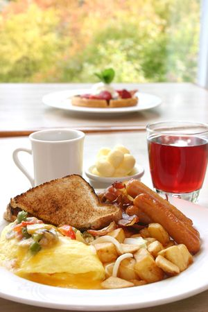 A power packed breakfast of omelette, sausages and bacon, accompanied by hash browns and toast. Served with choice of coffee or cranberry juice. Stock Photo